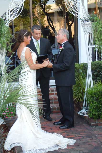 Couple being married by a minister in the Raintree Restaurant courtyard