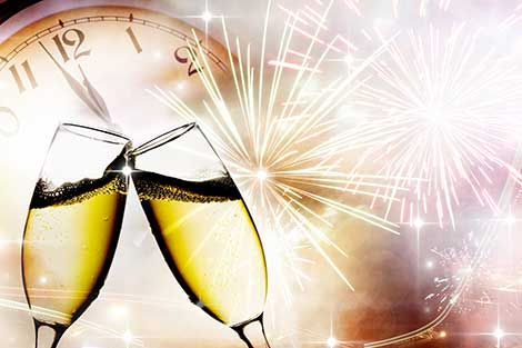 Symbols of New Year's Eve with clock, champagne, and fireworks
